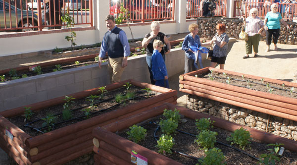 Strolling through the new Blanche Duggan Memorial Garden during its opening day are, from left: Phoenix Mayor Greg Stanton and his son, Trevor; Barbara Damiani, treasurer for the Loma Linda Neighborhood Association; Bessie Rudman, Blanche's sister; and three of Blanche's four daughters—Patty Duggan, Joan Felkins and Jean Boyce (photo by Teri Carnicelli).