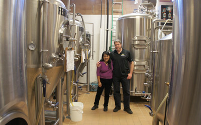Rob and Candy Berkner stand amidst the giant fermenting tanks in the building just behind their popular Sunnyslope brew pub, North Mountain Brewing Co., which celebrates its third anniversary this month (photo by Teri Carnicelli).