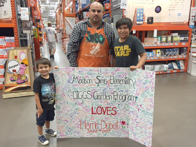 Madison Simis students Andy Ward-Garcia and Aaron Smith present a thank-you poster signed by students in the DIGGS program to Home Depot Store #0477 Assistant Manager Jose Sanchez, who helped with donations for the school gardens (submitted photo).