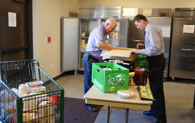 Mark McConnell, right, president of the St. Vincent de Paul Conference at St. Francis Xavier Parish, assists volunteer John Chilcott in unloading donations to the parish's food pantry from a nearby grocery store (photo by Teri Carnicelli).