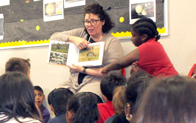 Arizona REALTOR® Kerry Melcher reads to children at the Harry & Sandy Rosenzweig Branch of the Boys & Girls Club in Phoenix as part of National Tell A Story Day on April 27 (submitted photo).