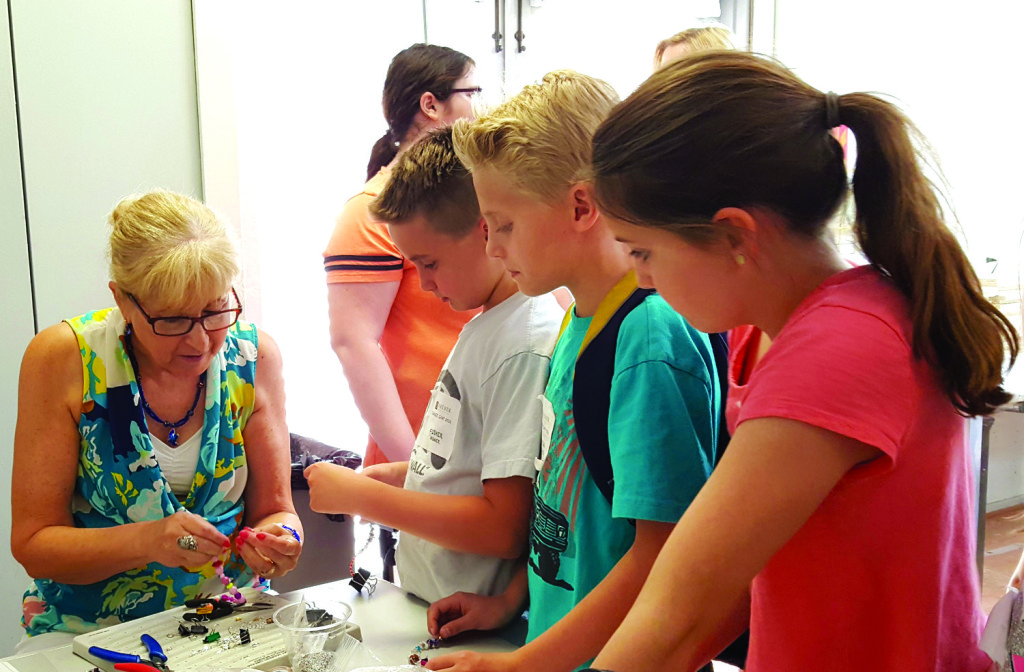 """North Central resident and jewelry designer Gerri Dames, who recently launched """"Gerri's Beading Parties,"""" teaches a group of kids how to make their own beaded bracelets during a workshop last month at the Shemer Art Center (submitted photo)."""