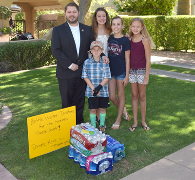 Clockwise from bottom left: Spencer Bodell, Cici McKenzie, Bailey Reynolds and Jules McKenzie show off some of the bottled water that they collected for the homeless last month to Congressman Ruben Gallego, who stopped by to cheer them on (submitted photo).