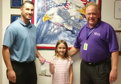 North Central third-grader Laine Parnell donates just over $100 in cash to Catholic Charities' MANA House, represented by Derek Kelley, MANA House senior programs manager (left) and Peter Fleckenstein, assistant house supervisor. She raised the money through lemonade and baked-goods sales this summer (submitted photo).