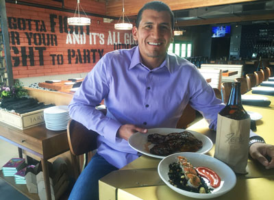 Rick Cordova, owner of Joe's Midnight Run, shows off some of the customer favorites including the Shrimp Arroz Negro, and the short ribs cooked Korean style. Patrons who order 40-ounce bottles of beer find them delivered in brown paper bags (photo by Patty Talahongva).