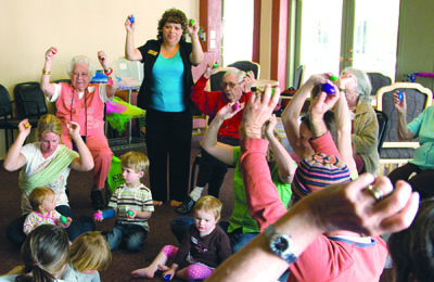 """Residents of The Terraces in Phoenix join in the music making with children and parents from Music Together as part of the early childhood music program's """"Generations"""" classes (submitted photo)."""