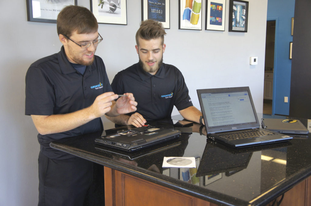 Noah Spencer, 25 (left) and Steven Winkler, 18, both managers at Generation Tech Support, examine a customer's older laptop computer to determine if the hard drive and memory can be upgraded (photo by Teri Carnicelli).