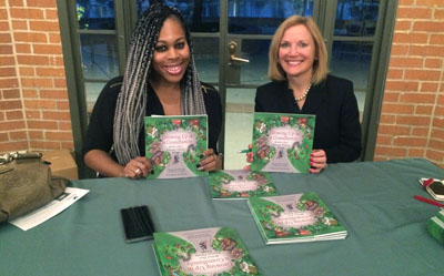 """ASU graduate student Brittany Avent and author Dr. Nichola Gutgold display their new children's book, """"Growing Up in a Grandfamily, Within Our Chosen Family Village"""" (photo courtesy of Duet)."""