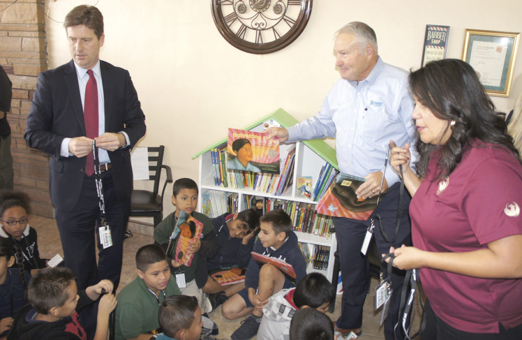 Celebrating the launch of a Little Free Library inside Roy's Barbershop at 19th Ave. and Osborn Road are some neighborhood schoolchildren from Maie Bartlett Heard School, along with (from left) Phoenix Mayor Greg Stanton, Jason Barlow, president and CEO of for Humanity of Central Arizona, and Dist. 4 Councilwoman Laura Pastor, who hand out free books and library lanyards to the children (photo by Teri Carnicelli).